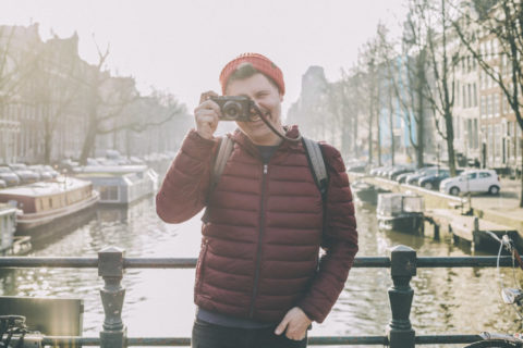 Tim Cochrane with camera facing the viewer on an Amsterdam canal bridge
