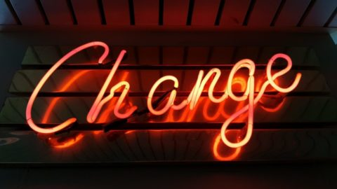 Change - orange neon sign on black background