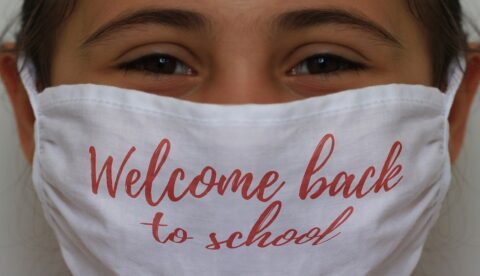 Young girl with face mask with message 'welcome back to school'