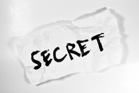 'Secret' handwritten on a white scrap of paper