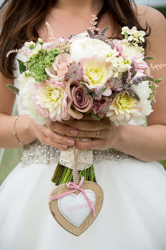 Wedding bouquet held by a bride in white - photo: Take Aim Photograph