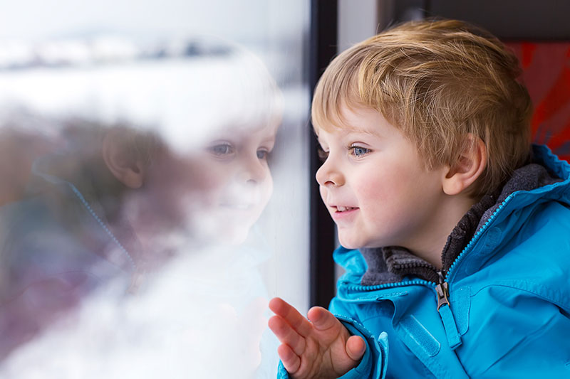 Young boy looks out a train window