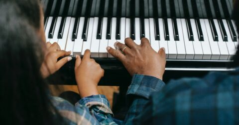 Father and child play piano.