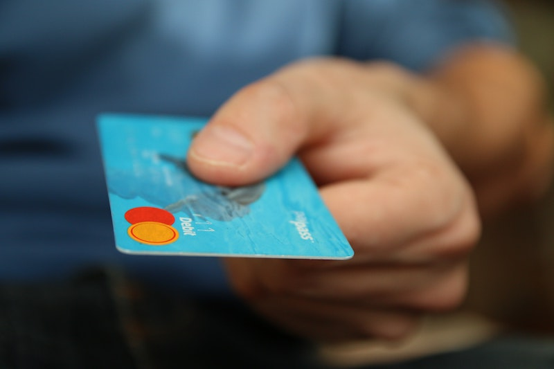 Person holds blue debit card.
