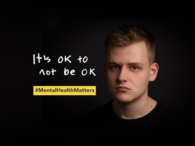 It's OK to not be OK - photo of young man against black background with mental health message alongside