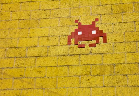 Space Invaders icon on a brick wall - photo: Pexels