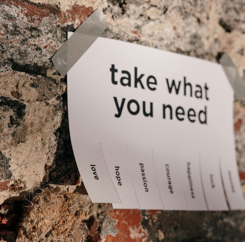 Take what you need - poster on a brick wall