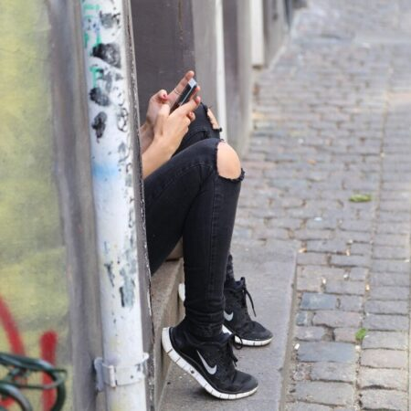 Teenage girl in black jeans on phone