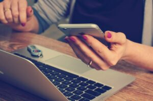 woman in office with laptop & phone by Firmbee from Pixabay