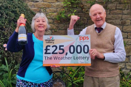 Two happy winners of The Weather Lottery with a £25,000 giant cheque