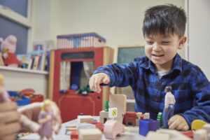 A young boy plays with wooden building blocks. Photo: NPSCC