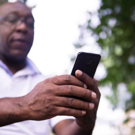 Middle-aged Black man looks at his mobile phone by Joshua Woroniecki from Pixabay