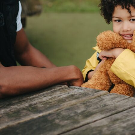 toddler with his dad sitting at a picnic table, hugging a teddy bear. Photo by Anete Lusina from Pexels