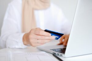 A woman holding her credit card to make a payment on her laptop by Anna Shvets from Pexels