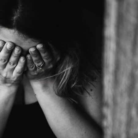 Woman with her head in her hands Photo by Kat Jayne from Pexels