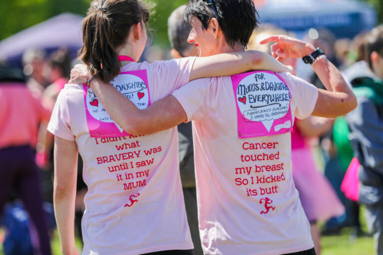 Mother and daughter participants in CRUK Race for Life, with messages on the back of their tshirts