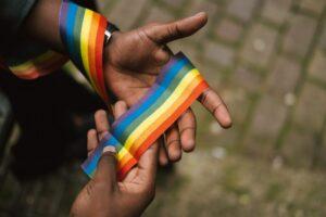 Black man's hands holding a rainbow ribbon - photo: Pexels