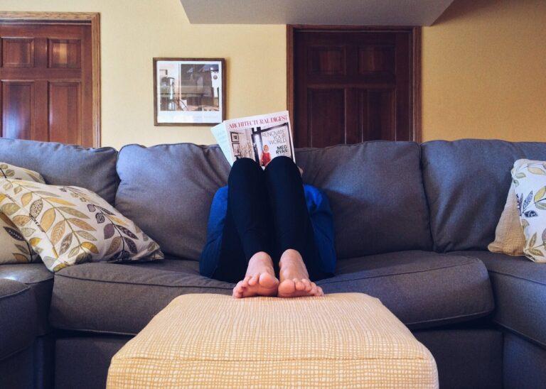 Someone lying back comfortably on a sofa reading a magazine. Photo: pexels.com