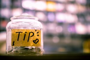 Tip jar with some banknotes in it. Photo: Unsplash
