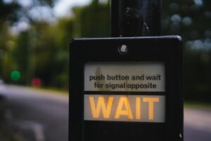Illuminated WAIT sign on a UK pedestrian crossing - photo: Pexels