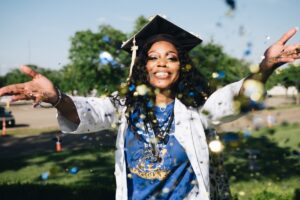 Woman with mortarboard celebrates graduating by throwing glitter - image: pexels.com
