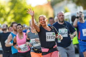 A woman runner smiles and raises her hand in the Ealing Half Marathon. Photo: George Blonsky