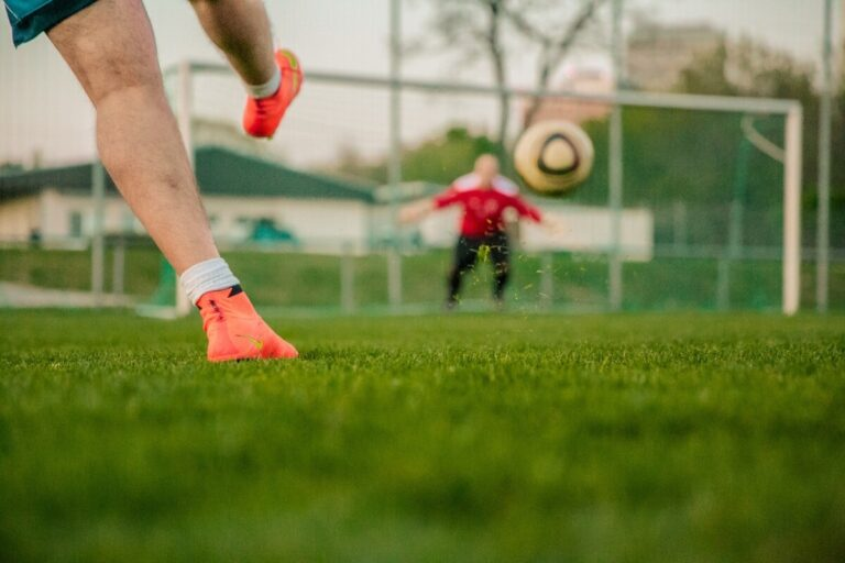 a man in orange boots kicks a football towards the net