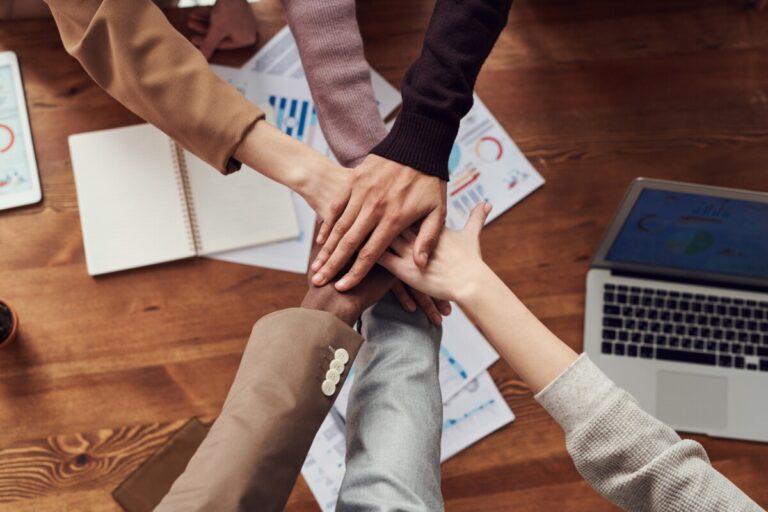 hands meeting over a desk symbolising teamwork