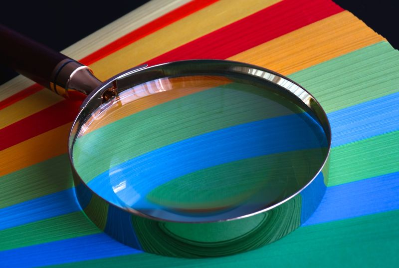 Magnifying glass laid on a fan of different colours