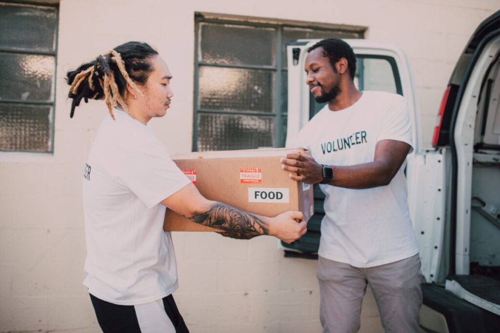 One volunteer hands another a food parcel out of a van.