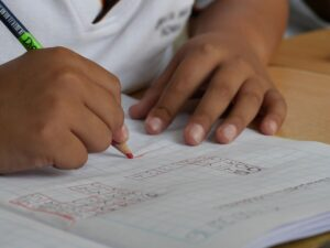 A school child doing maths in their exercise book