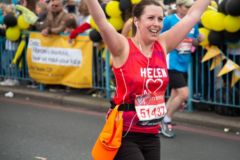 Helen, a BHF London Marathon runner in 2021, raises her arms in salute.
