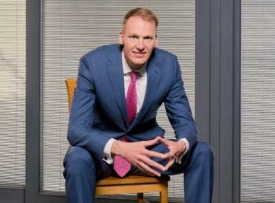 David Knott, the new CEO of the National Lottery Community Fund sits on a chair in a blue suit and pink tie