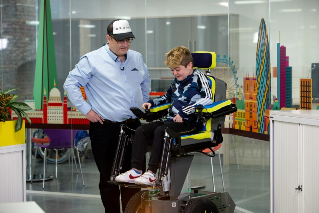 Eli tests out the new wheelchair with Wheels of Change project manager Frank Robertson. Photo: Whizz Kids