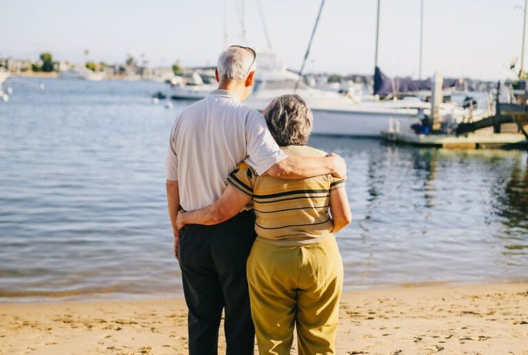 An older couple wrap their arms around each other and gaze at a boat from the sandy beach