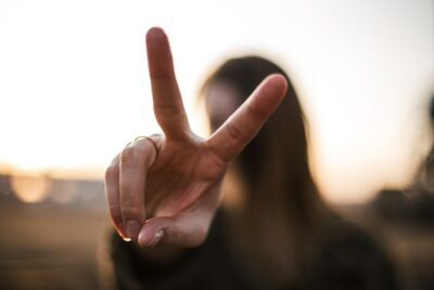 Woman (blurred in background) holding up two fingers suggesting victory or double. Photo: Unsplash